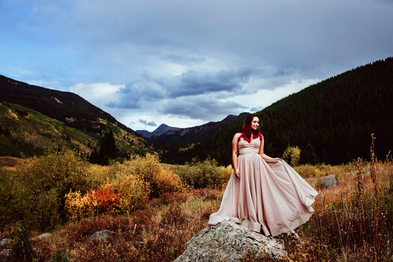 Senior Portrait, High School woman with magenta hair holds her pink dress up as she walks through mountain meadows