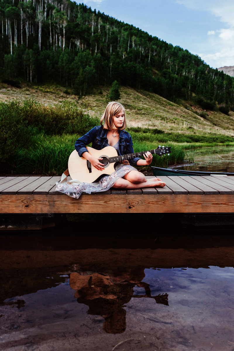 Senior Portrait, High School blonde woman sits on lake dock playing her guitar, forest is behind her