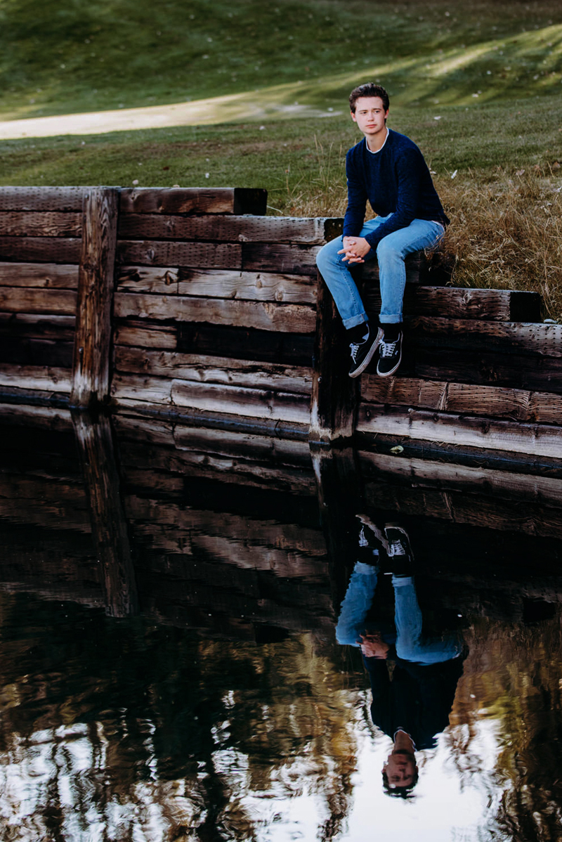 Senior Portrait, High School man sits on wooden plank wall beside a pond, his reflection is mirrored