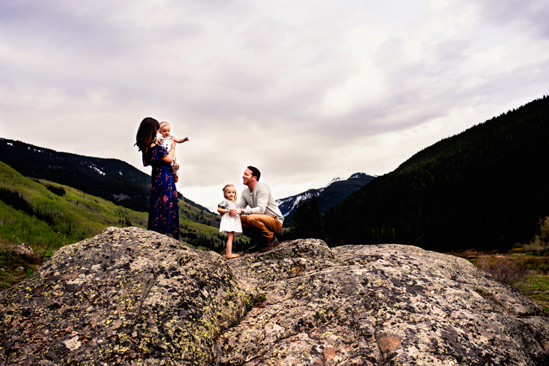 Family Photography, two parents hold their toddler daughters near atop a rock on a green mountainside