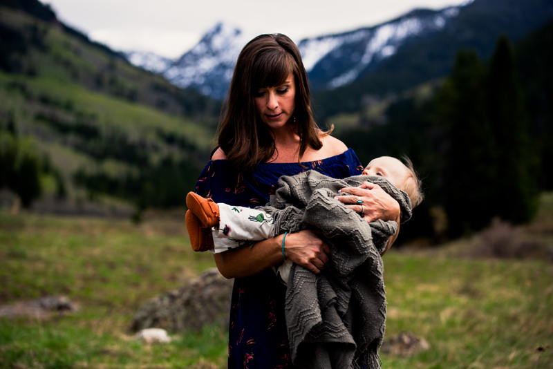 Family photography, mother holds bundled sleeping toddler in a grassy mountain meadow