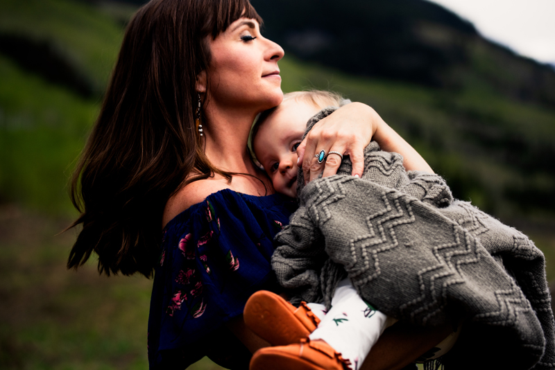Family Photography, happy young brunette woman holds her toddler child close outdoors