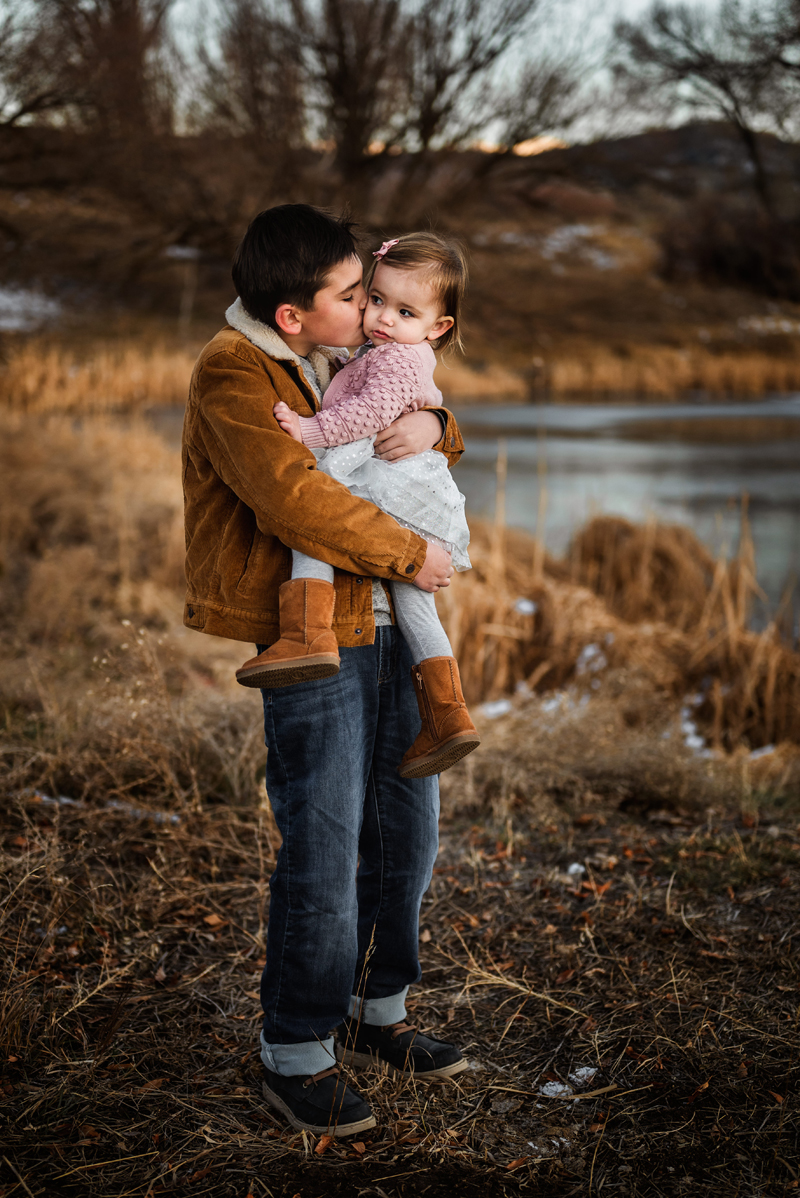 Family photography, young boy holds up toddler daughter and kisses her, they stand beside country lake