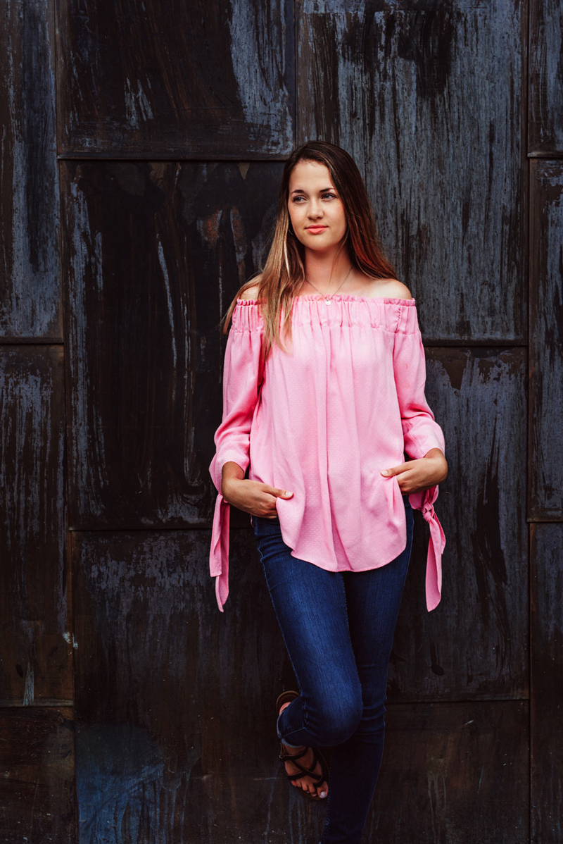 Senior Portrait, High School woman in pink blouse and blue jeans leans against an old barn door