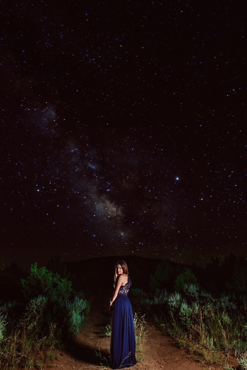 Senior Portrait, High School woman in royal blue dress looks back as she walks on trail, a star filled sky behind her