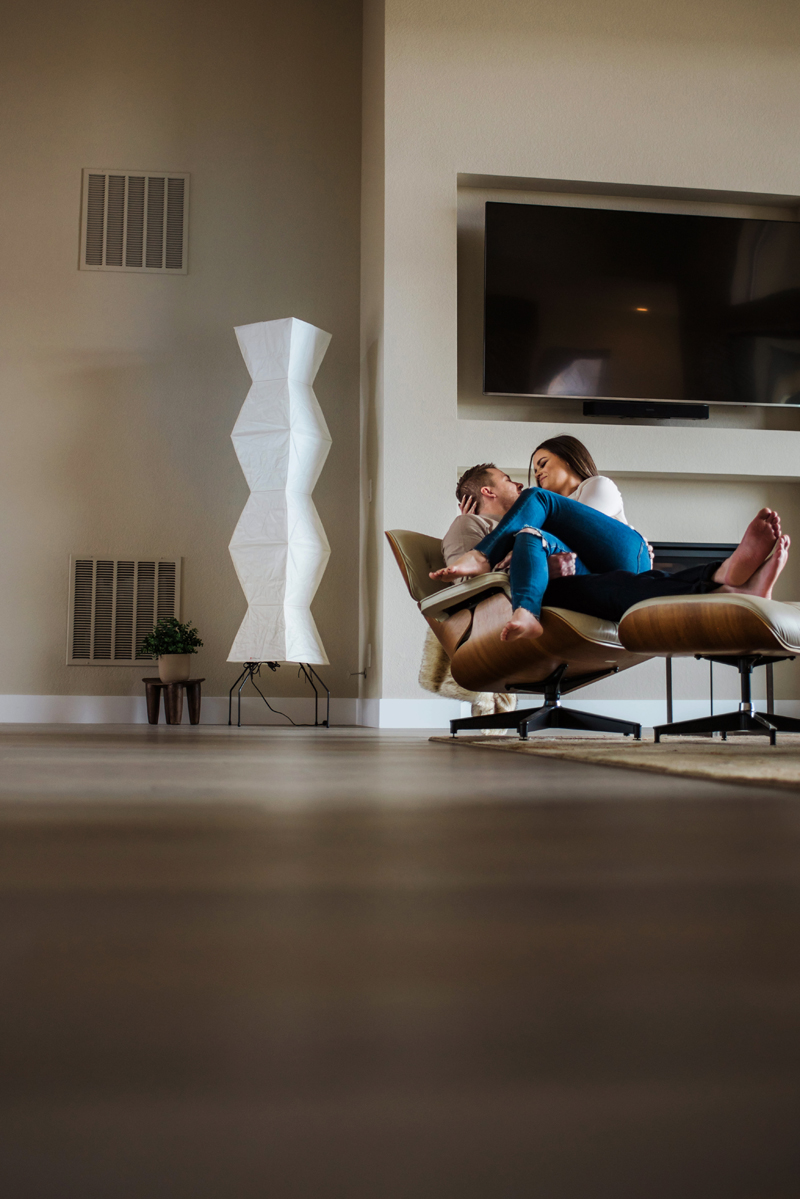 Family Photographer, in a modern city apartment a man holds his wife on their lounging chair, his feet on the matching lather ottoman