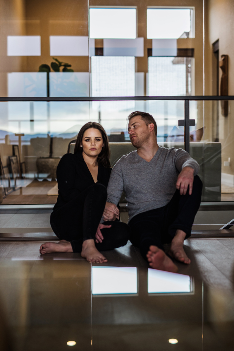 Family photography, professional looking couple sit on the floor of a modern city apartment