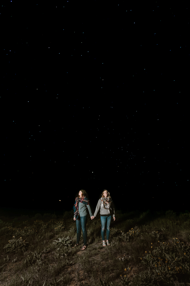 LGBTQ+ Couple, two women bundled in scarves hold hands in a meadow on a dark night