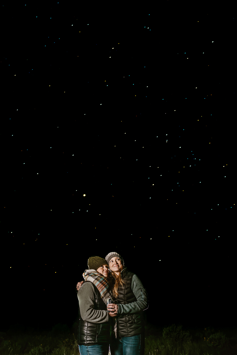 LGBTQ+ Couple, two women bundled in jackets and scarves look up at a star filled sky