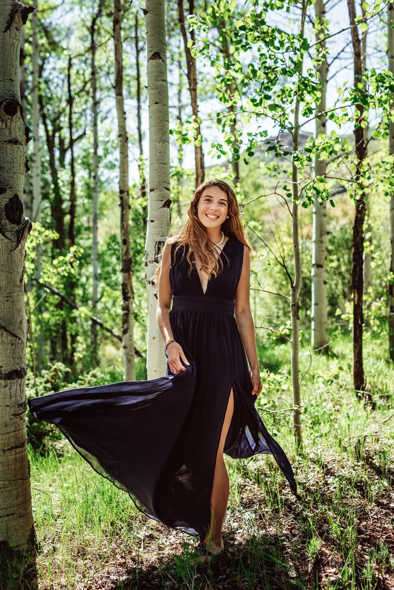 Senior Portrait, High School brunette woman walks through aspen forest, her dark dress flows with wind