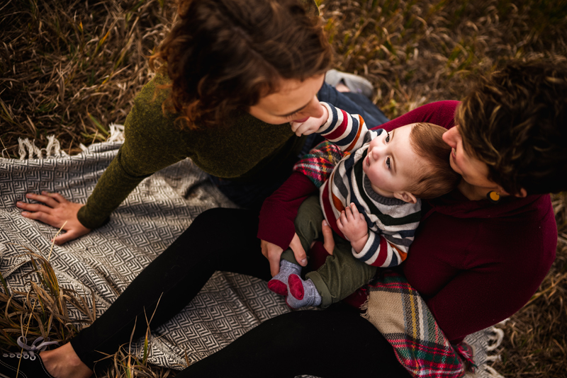 LGBTQ+family, two moms hold and admire their young baby as they sit on a blanket in the grass