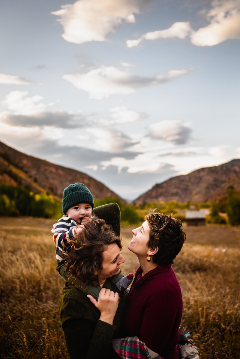 LGBTQ+ Family, a young baby rides on a mother's shoulders hiking trails as the other mother smiles at them