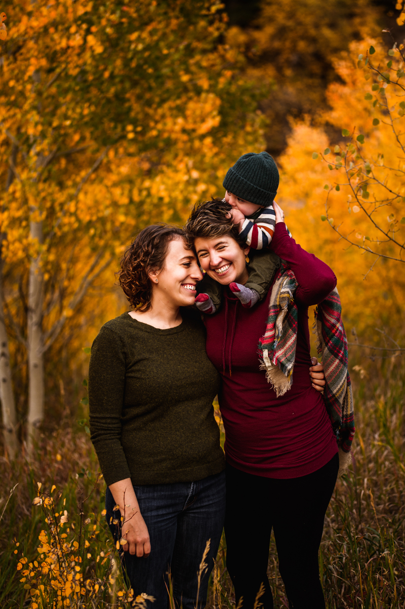 LGBTQ+ Family, Two mothers smile as their baby rides atop one mother's shoulders, they walk through a golden aspen forest in the fall