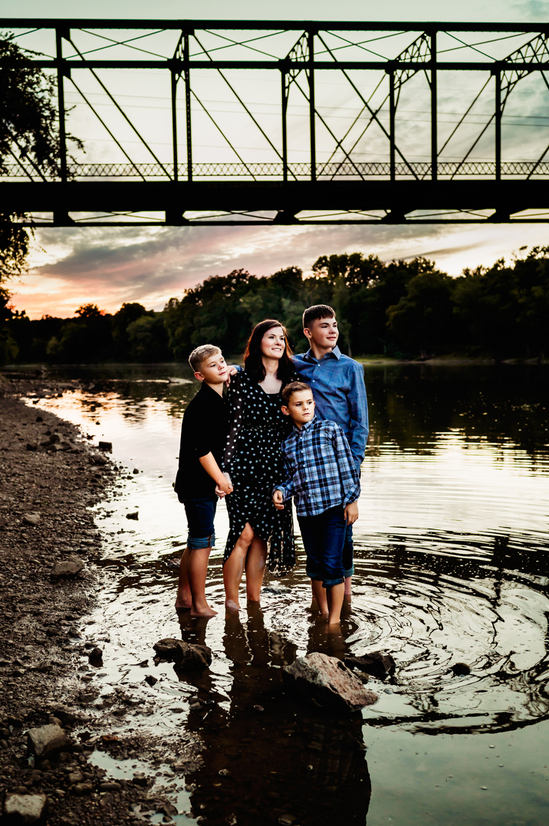 Family photography, mother stands with three sons barefoot in a quiet river, a bridge behind them