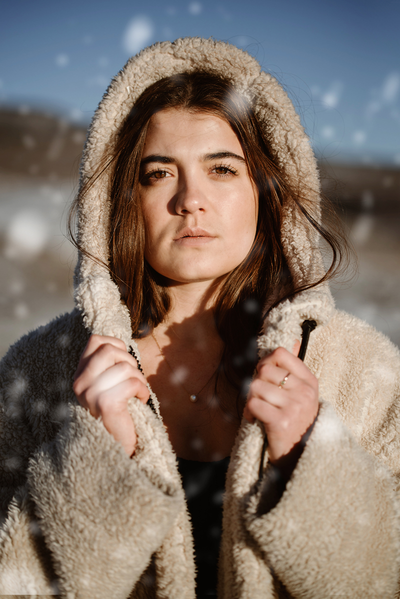 Senior Portrait, High School woman holds tight the wool parka style coat she wears while it snows